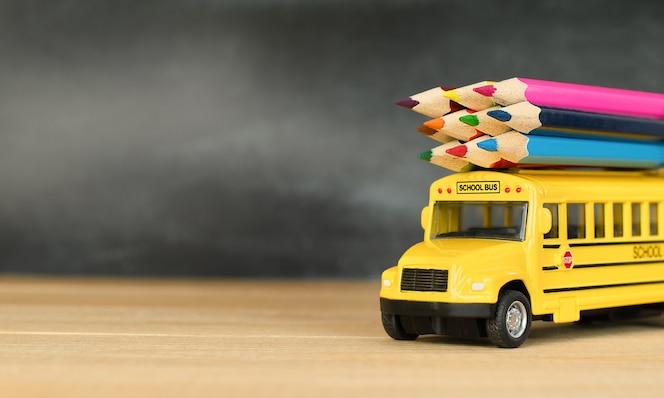 Speelgoedschoolbus met kleurpotloden op houten tafel in de klas
