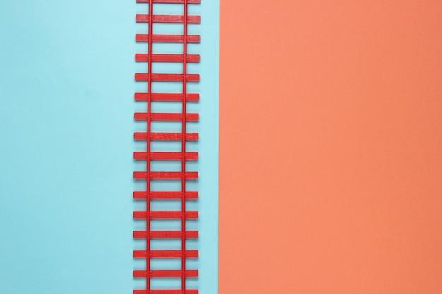Speelgoedspoorweg op een pastel achtergrond. vrachtvervoer, metafoor. industriële minimalistische achtergrond.
