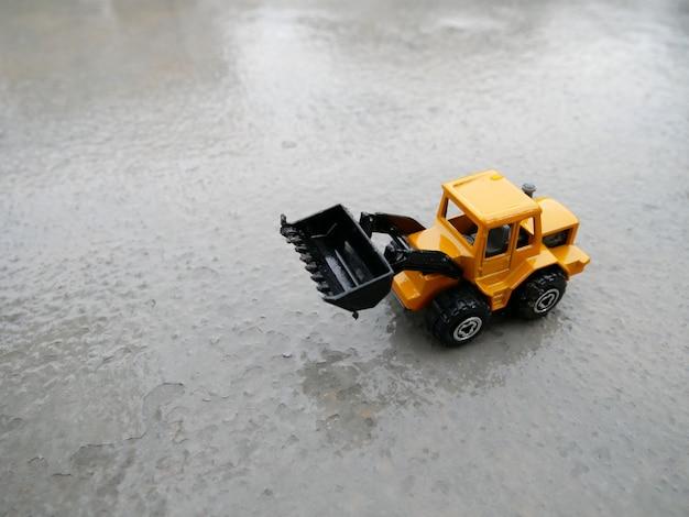 Speelgoedtractor op beton. model van de tractor op het beton.