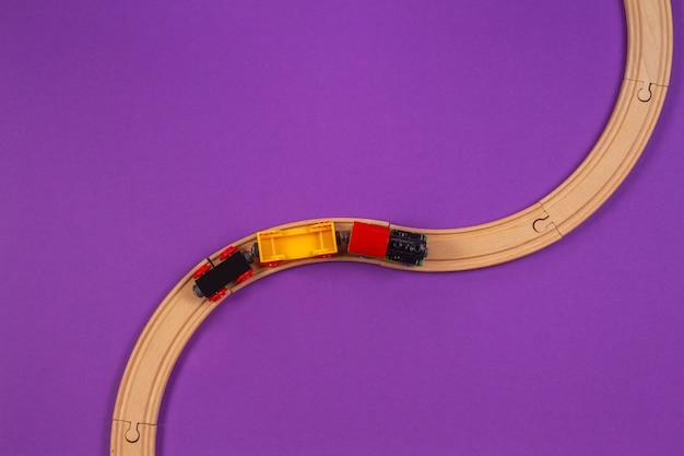Speelgoedtrein en houten rails op paarse achtergrond. bovenaanzicht