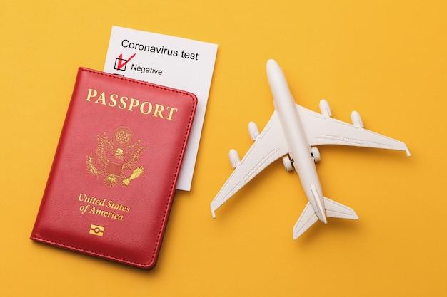 Speelgoedvliegtuig amerikaans paspoort en coronavirus testresultaten op een geel oppervlak