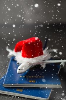 Speelgoedvliegtuig met paspoorten en santa claus-hoed.