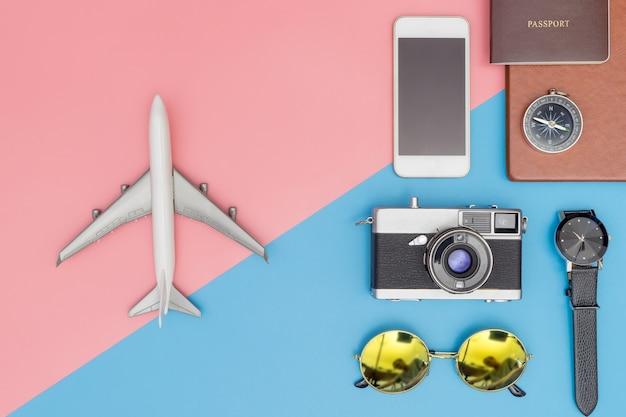 Speelgoedvliegtuig met reisvoorwerpen op de blauwe en roze pastelkleurachtergrond