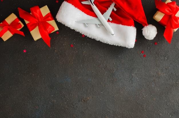 Speelgoedvliegtuig op kerstmuts en geschenkdozen op donker beton.