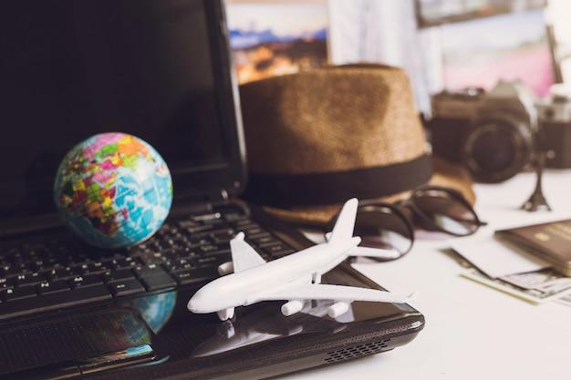 Speelgoedvliegtuig op laptop toetsenbord met globe en camera