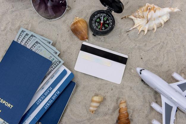 Speelgoedvliegtuig, paspoort, dollarbankbiljetten en creditcard op het zand