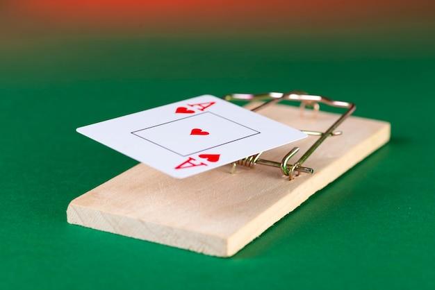 Speelkaart en muizenval, spelval, op een groene achtergrond, raken gokverslaving.