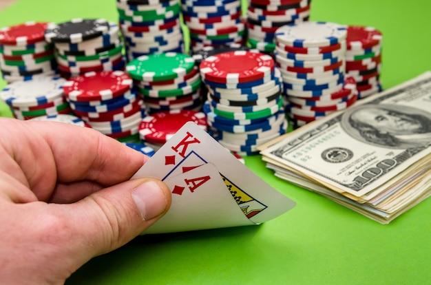 Speelkaartcombinatie in iemands hand, op groene achtergrond