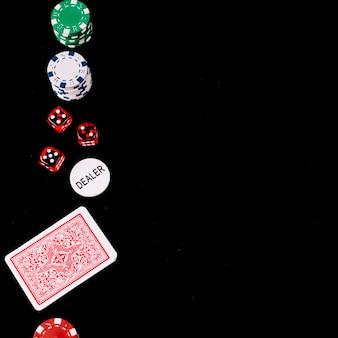 Speelkaarten; dobbelsteen; poker en dealer chips op zwarte achtergrond