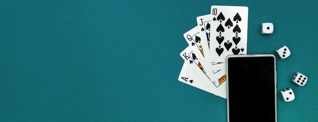 Speelkaarten poker dobbelstenen en telefoon op groen blauw doek panorama