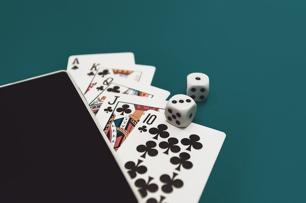 Speelkaarten poker dobbelstenen en telefoon op groenblauwe doek
