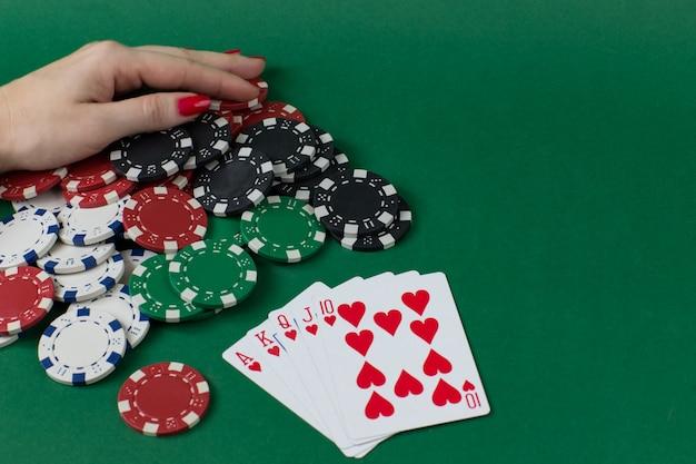 Speelkaarten, pokerfiches en een vrouwelijke hand