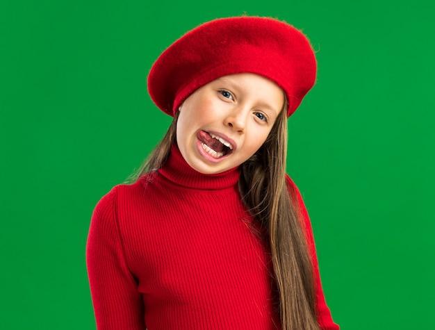 Speels blond meisje met rode baret die tong toont die op groene muur wordt geïsoleerd