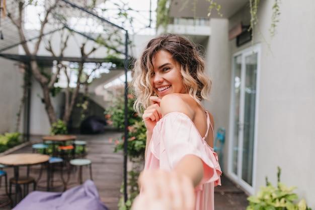 Speels blondemeisje dat over schouder met verlegen glimlach kijkt. buiten foto van koelende kaukasische vrouwelijke model met plezier in straatcafé.