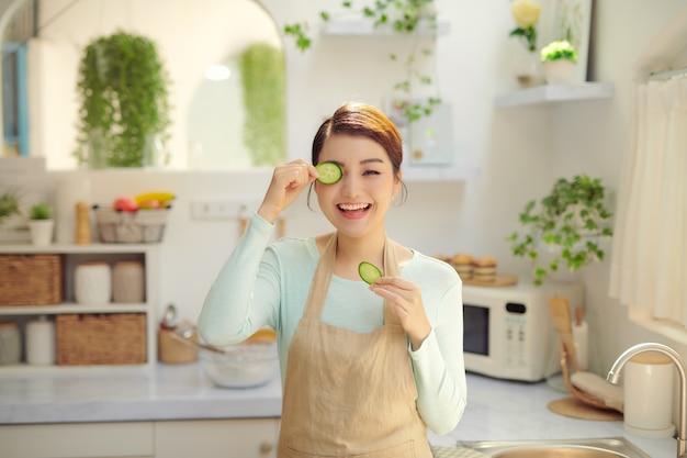 Speels één oog bedekken met een plakje komkommer, glimlachend naar de camera kijkend