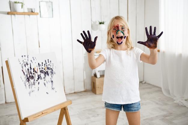 Speels en lachend blond meisje dat pret heeft, die van kunstactiviteiten geniet