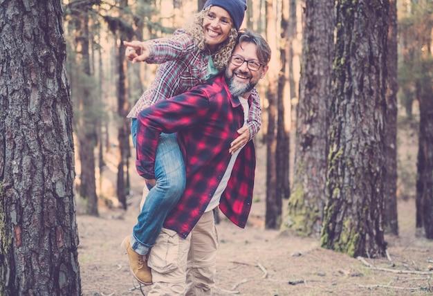Speels gelukkig knap kaukasisch paar dat op de rug meelift tijdens het wandelen op het pad in het bos. avontuur in de natuur concept - jonge volwassen man en vrouw genieten samen van vrije tijd in de buitenlucht