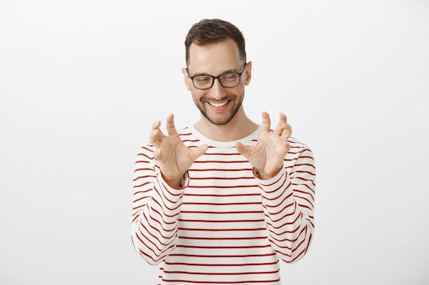 Speels grappig europees mannelijk model in gestreepte trui en bril, opzij kijkend terwijl blozend en vrolijk lachend