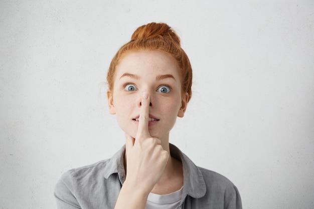 Speels grappig kaukasisch tienermeisje met gekke uitgeklapte ogen die vinger tegen neus drukken, waardoor ze eruitziet als een varken, gek spelen en plezier hebben binnenshuis