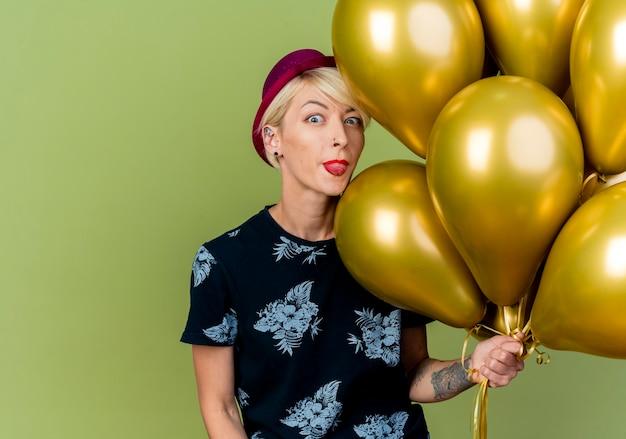 Speels jong blond partijmeisje die partijhoed dragen die ballons houden die camera bekijken die tong toont die op olijfgroene achtergrond met exemplaarruimte wordt geïsoleerd