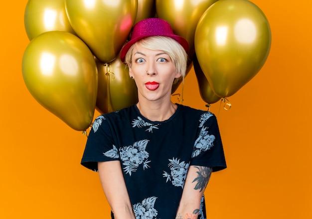 Speels jong blond partijmeisje die partijhoed dragen die zich voor ballons bevinden die camera bekijken die tong toont die op oranje achtergrond wordt geïsoleerd