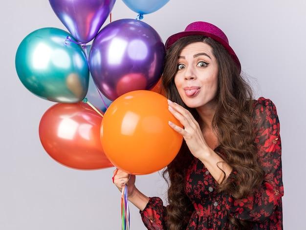 Speels jong feestmeisje met een feestmuts met ballonnen die de hand op een tong zetten die op een witte muur wordt geïsoleerd