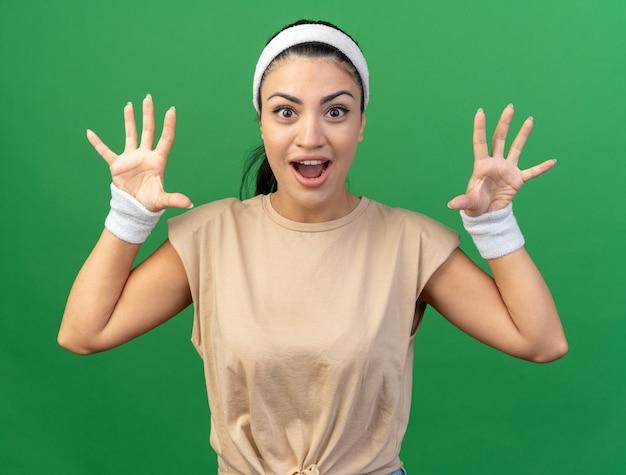 Speels jong kaukasisch sportief meisje die hoofdband en polsbandjes dragen die tijgergebrul en potengebaar doen dat op groene muur wordt geïsoleerd