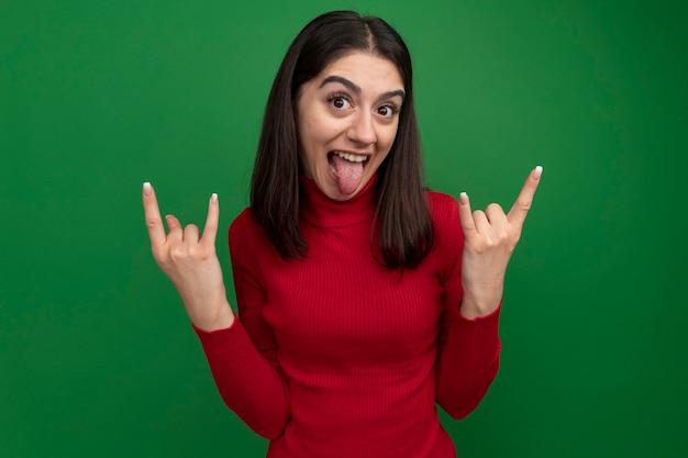 Speels jong vrij kaukasisch meisje die rotsteken doen dat tong toont die op groene muur wordt geïsoleerd