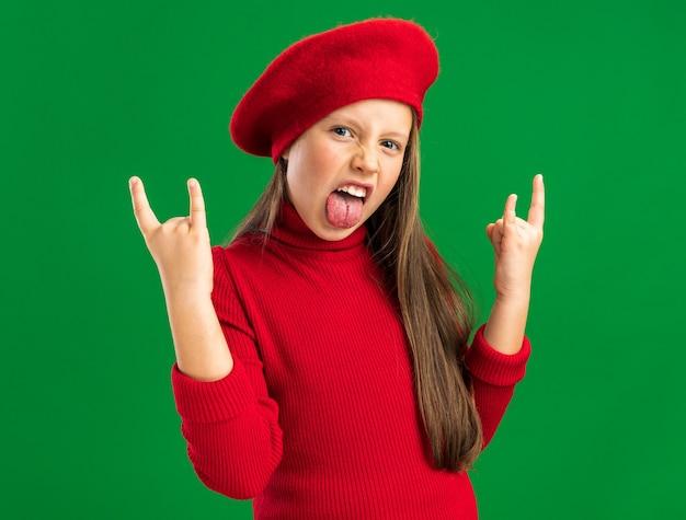 Speels klein blond meisje met een rode baret die een rotsbord doet met een tong die naar een camera kijkt die op een groene muur is geïsoleerd