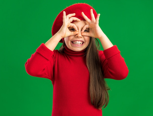 Speels klein blond meisje met een rode baret die naar de voorkant kijkt en een gebaar maakt met handen als verrekijker geïsoleerd op een groene muur