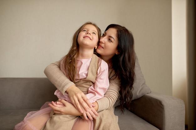 Speels klein meisje en jonge gelukkige moeder dromen samen, perfect weekend thuis. ze omhelzen elkaar stevig met liefde.
