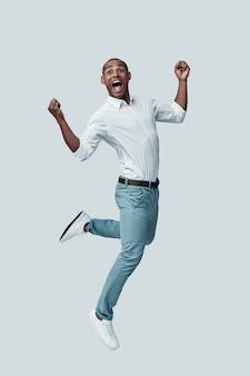 Speels. knappe jonge afrikaanse man die een gezicht trekt terwijl hij tegen een grijze achtergrond zweeft