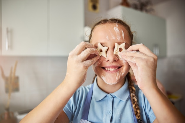 Speels meisje dat plezier heeft met deeg voor koekjes