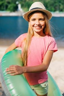 Speels meisje dat zich met zwemmende ring op kust bevindt