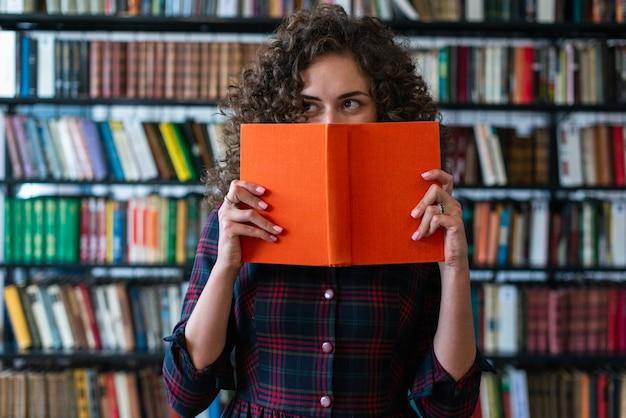 Speels meisje die een boek houden die haar gezicht behandelen en weg aan de kant kijken. blik boek met harde kaft