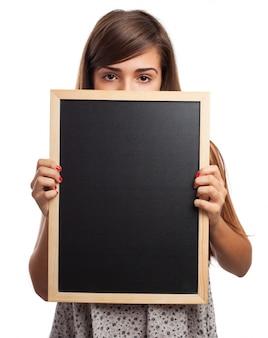 Speels meisje die een deel van haar gezicht met een schoolbord