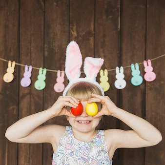Speels meisje in konijntjesoren met eieren