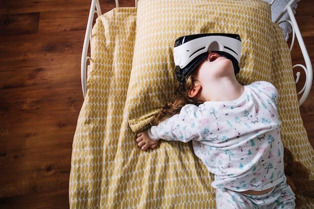 Speels meisje in vr-beschermende brillen op bed