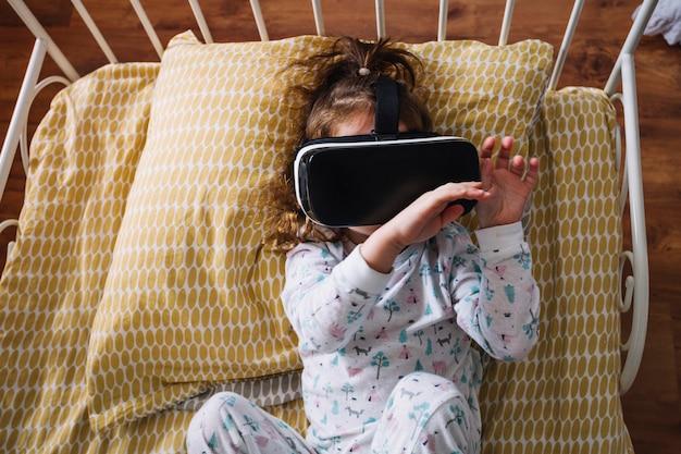 Speels meisje in vr-bril op bed