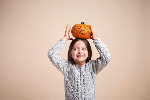 Speels meisje met halloween-pompoen op haar hoofd