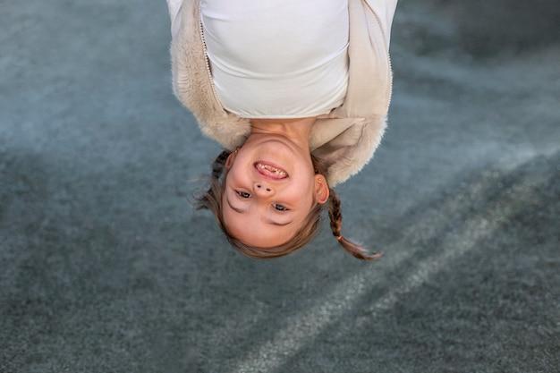 Speels meisje met ondersteboven hoofd
