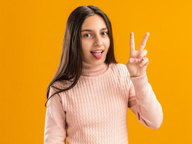Speels mooi tienermeisje die vredesteken maken die tong tonen die op oranje muur wordt geïsoleerd