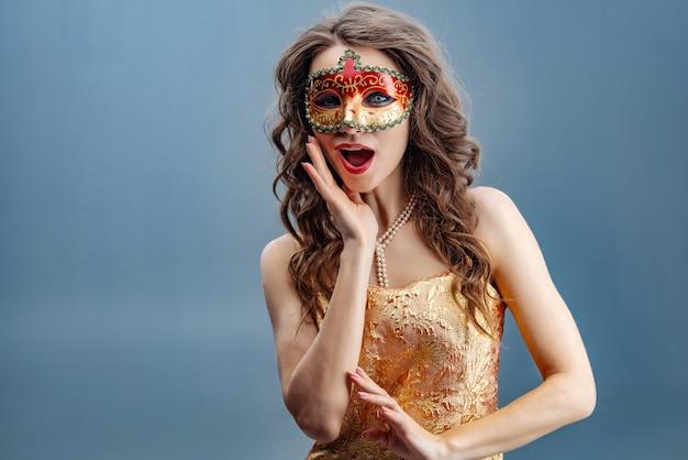 Speels op zoek meisje in een carnaval masker op een blauwe achtergrond