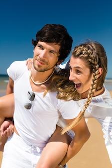 Speels paar op het oceaanstrand dat van hun zomervakantie geniet, de man draagt het vrouwenvervoer per kangoeroewagen
