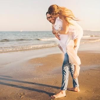 Speels paar op het oceaanstrand die van hun de zomervakantie genieten