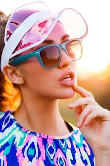 Speels slank meisje in stijlvolle kleurrijke crop top, transparante pet en zonnebril poseren op straat bij zonsondergang.