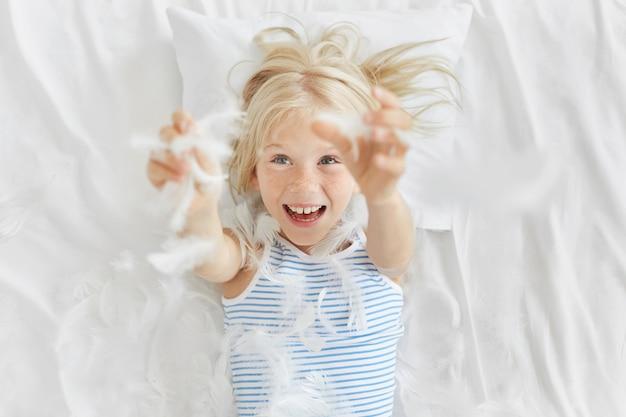 Speels sproetig schattig meisje met blauwe ogen, veren prikkend na het in stukken scheuren van het kussen, lol maken voordat ze naar de kleuterschool gaan. het kleine meisje spelen met veren op wit beddengoed.
