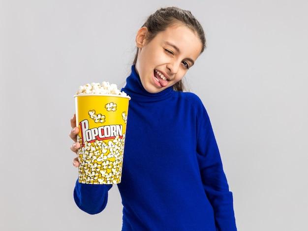 Speels tienermeisje dat een emmer popcorn uitrekt naar de camera die naar de voorkant kijkt en een tong toont die op een witte muur wordt geïsoleerd