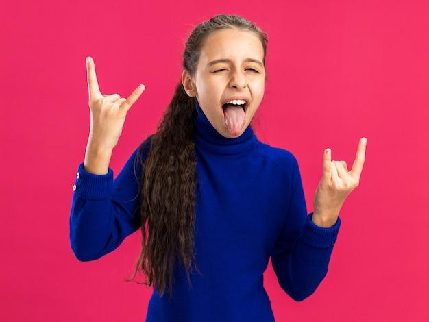 Speels tienermeisje dat naar de camera kijkt en een rotsbord doet knipogen met tong geïsoleerd op roze muur