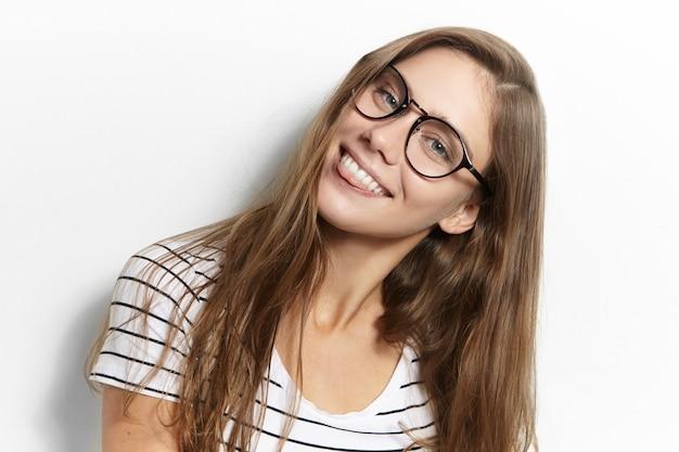 Speels tienermeisje in brillen die voor de gek houdt, kijkt en haar tong uitsteekt alsof ze je plaagt. kinderachtig vrouwelijk poseren, tong tonen, goed humeur hebben